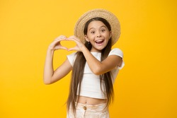 happy kid show heart gesture. she love summer vacation. spring fashion for kids. childhood happiness. cheerful little girl wear straw hat. ready for beach party. small beauty.