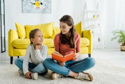 happy kid sitting on carpet with babysitter holding book