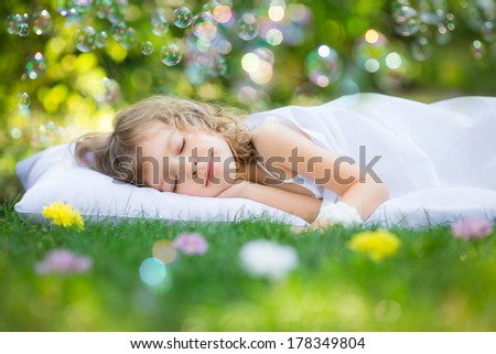 Happy kid sleeping on green grass outdoors in spring garden