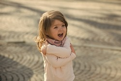 Happy kid smile with hug hand gesture on sunny day on grey pavement outdoor. Child, innocence, childhood concept.