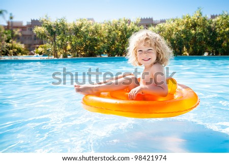 Happy kid swimming in blue water of pool on a tropical resort at the sea. Summer vacations