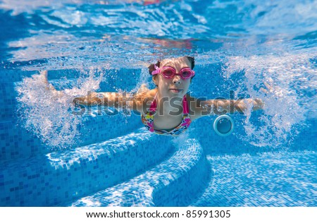 Happy kid swimming underwater in pool. Active girl swims and having fun. Child sport on summer vacation