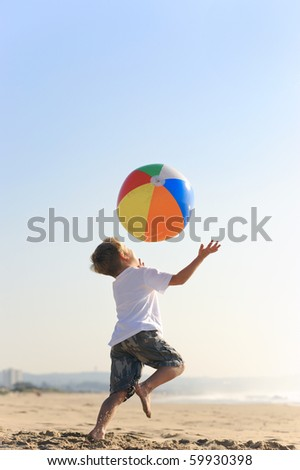 Happy kid throws his beach ball in the air and tries to catch it