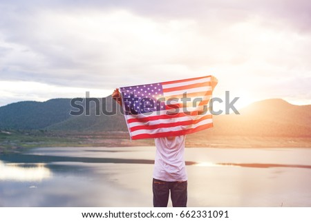 Shutterstock Happy kid with a hande held American flag in standing in the summer sunshine. USA celebrate 4th of July- Independence Day.