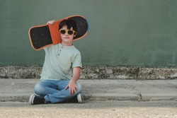 happy kid with skateboard and sunglasses sitting on the street