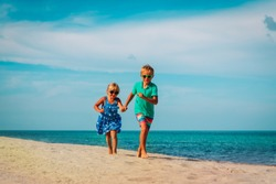 happy kids- boy and girl running at beach