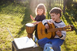 Happy kids brother and sister having fun with musical instruments together outdoors. Kid  boy playing  guitar and watching  online lessons  on laptop while practicing. quarantine.