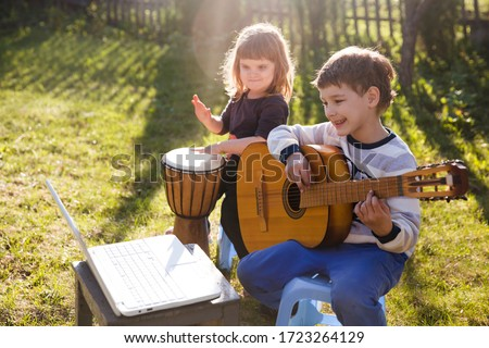Happy kids brother and sister having fun with musical instruments together outdoors. Kid  boy playing  guitar and watching  online lessons  on laptop while practicing. quarantine.  Foto d'archivio ©