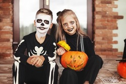 Happy kids celebrate halloween on the street near the house in costumes and make-up with pumpkin lantern jack,