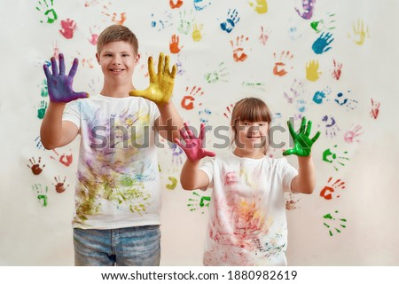 Happy kids, disabled boy and girl with Down syndrome smiling at camera, showing their hands painted in colorful paints for hand prints on the wall. Children with disabilities and special need concept Foto stock ©