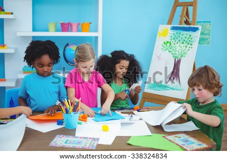Happy kids doing arts and crafts together at their desk