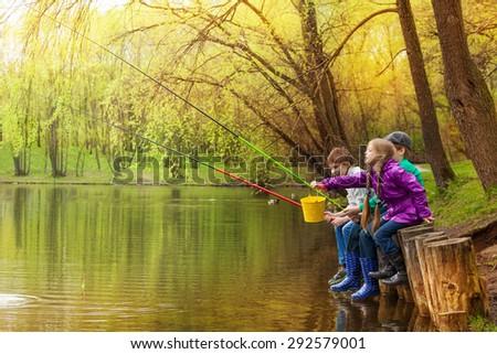 Happy kids fishing together near beautiful pond