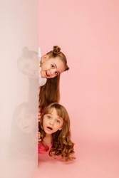 Happy kids, girls isolated on coral pink studio background. Look happy, cheerful. Copyspace for ad. Childhood, education, emotions, business, facial expression concept. Peeking out from behind the
