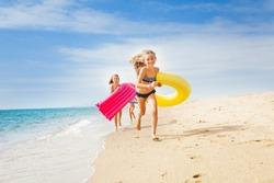 Happy kids having a race on sunny beach in summer