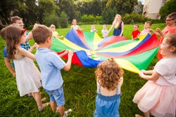 Happy kids holding parachute during funny game