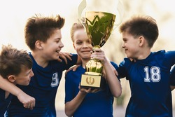 Happy Kids in Sports Team Celebrating Success in School Tournament. Young Caucasian Boys Holding Golden Trophy. Children in Youth Soccer Team Winning Junior Competition