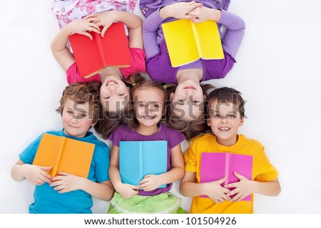 Happy kids laying on the floor holding books - the colorful world of reading