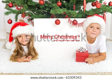 Happy kids laying under the christmas tree with a white banner for text