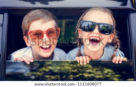 Happy kids looking out the car window