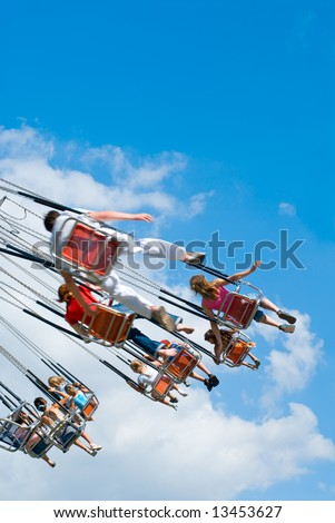 Happy kids on swinging carousel at blue cloudy sky