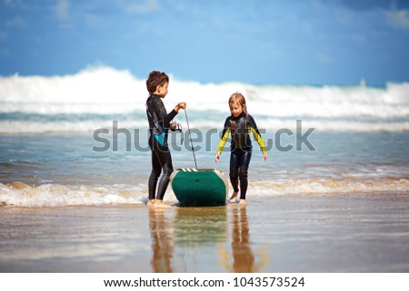 Happy kids play, run and ride on the body board. Children and surfing concept, surfing in a wet suit.