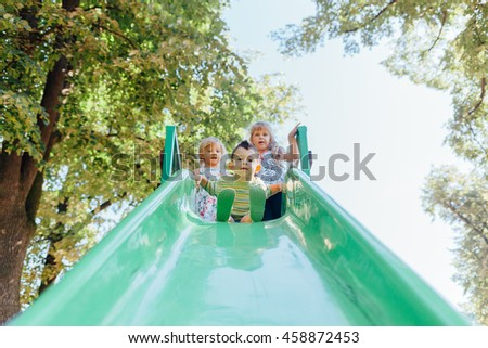 Happy kids playing at the playground  outdoors. Children at the toboggan. #458872453