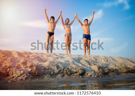 happy kids playing on beach at the sunrise time #1172576410