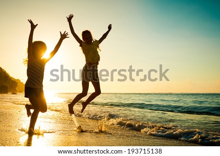 happy kids playing on beach at the sunrise time