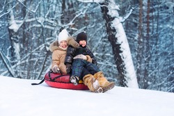 Happy kids slide down the hill. Forest and a lot of snow. Cold winter.