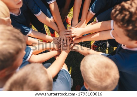 Happy kids sports team stacking hands at the field. Children team sports. Boys at sports camp stacking hands before a match. School age children in a team