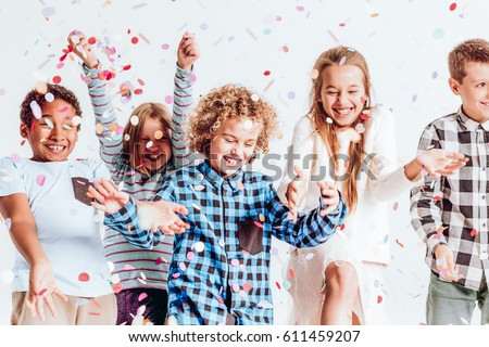 Happy kids throwing colorful confetti in a room #611459207