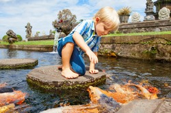 Happy kids walk with fun by pond stepping stones, feeding golden koi fishes in Tirta Gangga garden with natural water pools. Culture, arts of Bali, popular travel destination in Indonesia.