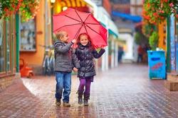 happy kids walking under the rain on colorful street