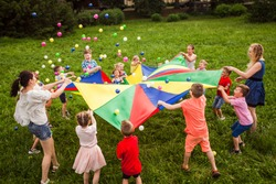 Happy kids waving rainbow parachute full of balls