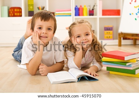 Happy kids with colorful books laying on the floor in their home