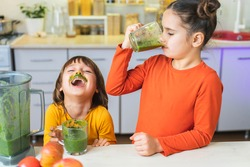 Happy Kids with glass cup of green smoothies in hands. Cute boy and girl crazy drinks healthy dietary nutritious cocktail at home in the kitchen. Healthy lifestyle, raw food