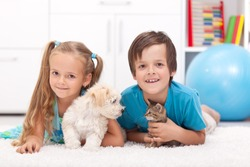 Happy kids with their pets - a dog and a kitten, laying on the floor