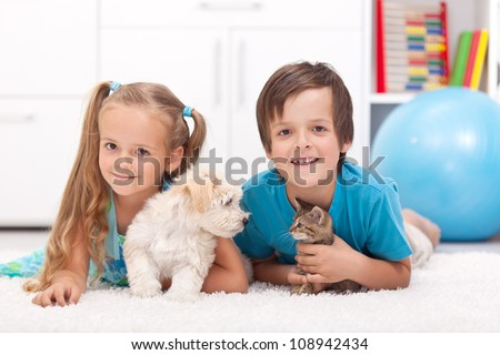 Happy kids with their pets - a dog and a kitten, laying on the floor - stock photo