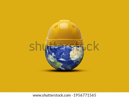 Happy Labor Day concept yellow background. 3D Earth with yellow helmet isolated on yellow background. 1st May Labour day celebration.