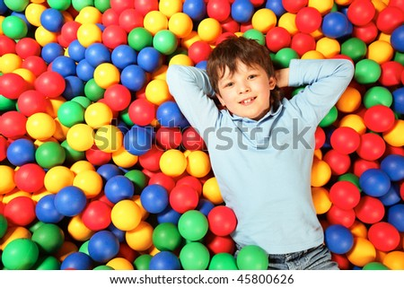 Happy lad lying on colorful balls and looking at camera with smile