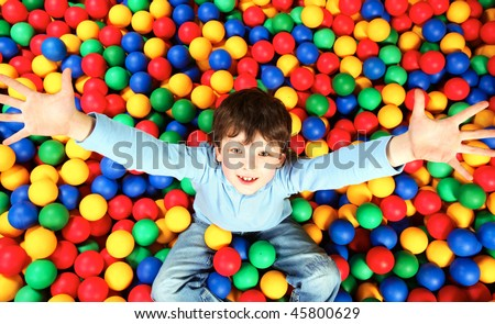 Happy lad seated on colorful balls and stretching arms to camera