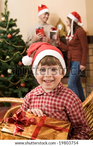 Happy lad with gift in hands looking at camera with smile on Christmas day