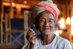Happy lady of Pa'O ethnic minority smoking a Burmese cigar and smiling at Indein village near Inle Lake, Shan State, Myanmar.