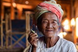 Happy lady of Pa'O ethnic minority smoking a Burmese cigar and smiling at Indein village near Inle Lake, Shan State, Myanmar.