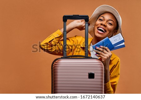 Happy lady with earrings behind the luggage with tickets laughs Photo stock ©