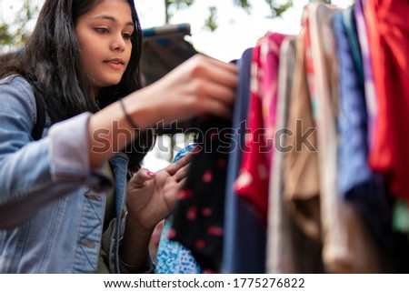 Happy late teen girl looking and buying clothes from outdoor street market of Delhi, India at day time. Shoot location Sarojini Nagar, Delhi, India.
