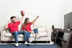 Happy Latin boyfriend and girlfriend watching American football match on TV at home