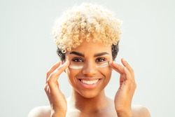 Happy latin brazilian woman with healthy skin applying tone cream on her face on white studio background. she covers bags under the eyes