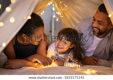 Happy latin daughter with african mom and indian dad playing in kid tent. Little girl talking to mother and father lying on bed in hut. Funny cute girl with multiethnic parent in cozy shelter at home.