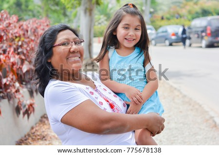 Happy latin mom and little daughter outside.